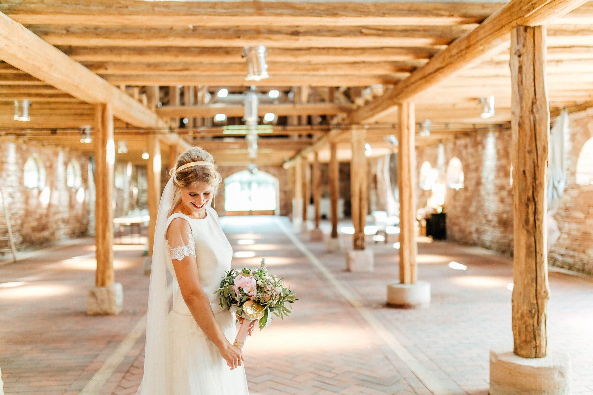 Holzbalken Braut Blumen Schleier lachen