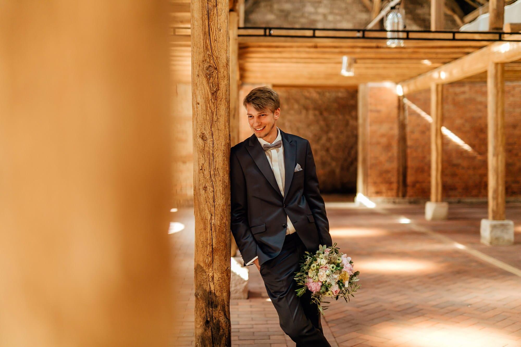 Bräutigam Brautstrauß Anzug lachen Holzbalken