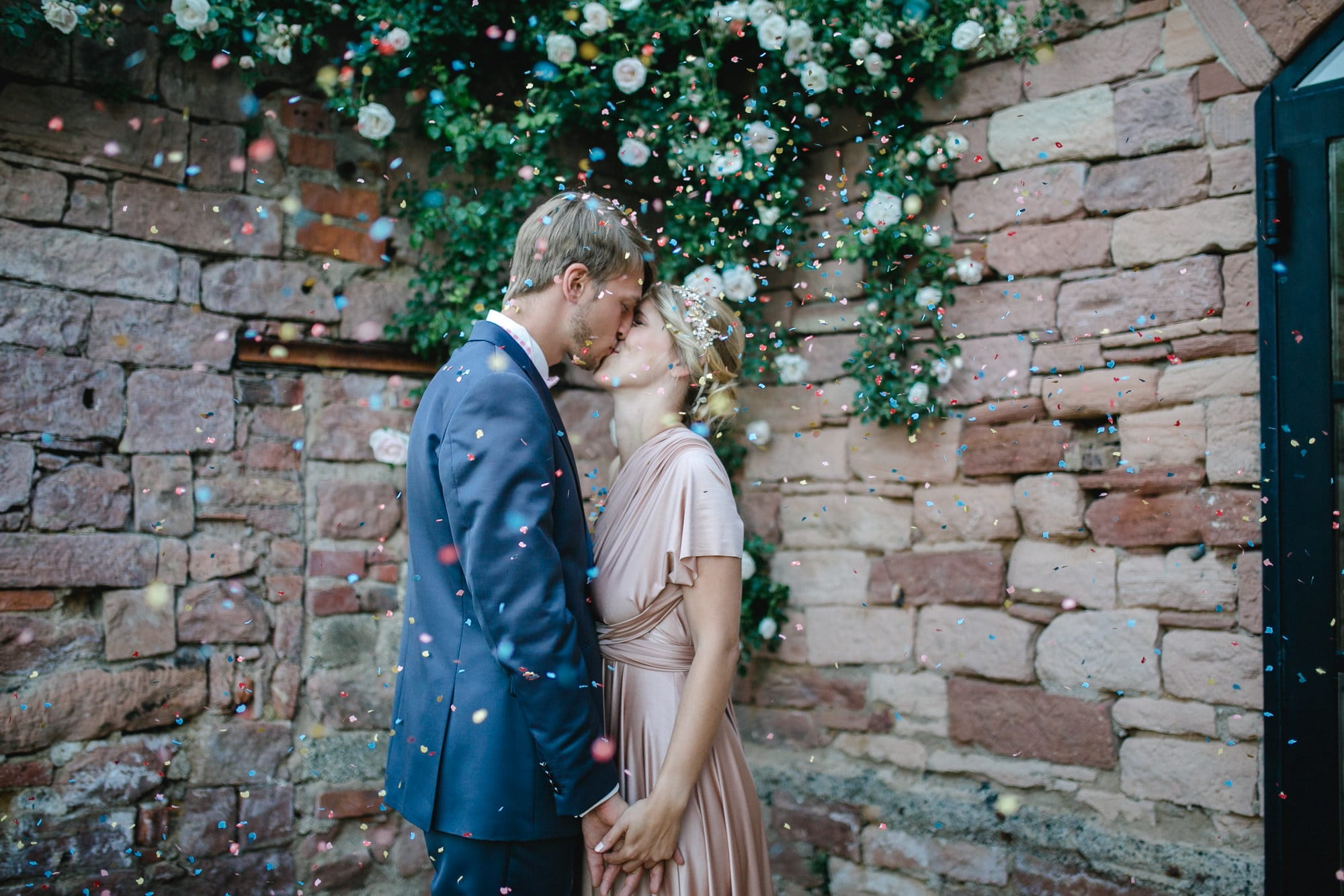 Brautpaar kuss Konfetti Steinmauer Blumen