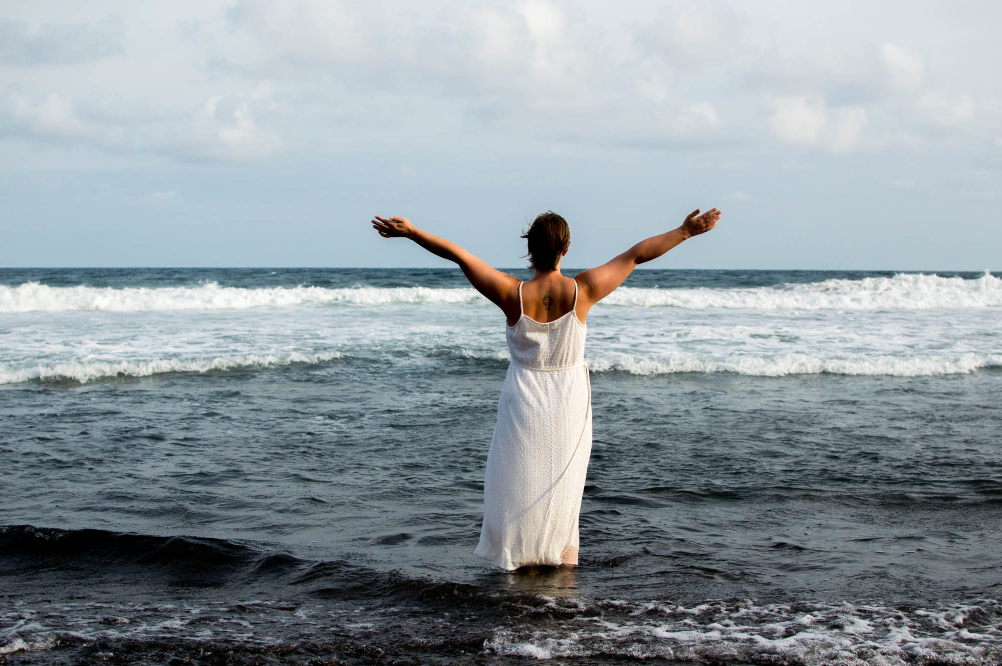 Bali Reisebericht Christine Raab am Meer von hinten im weißen Kleid Freiheit