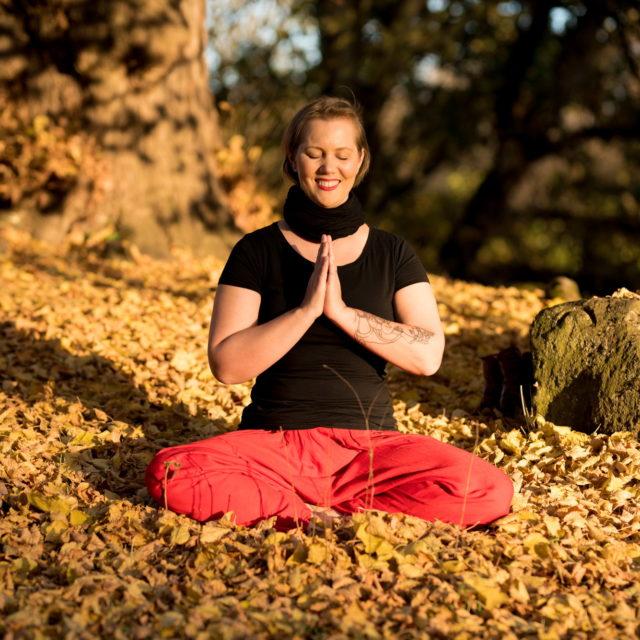 Christine sitzt in der Sonne im Meditationssitz im Herbst mit roter Hose und lacht