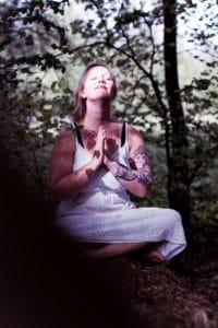 Christine hält die Hände in Namaste und lässt sich die Sonne ins Gesicht scheinen